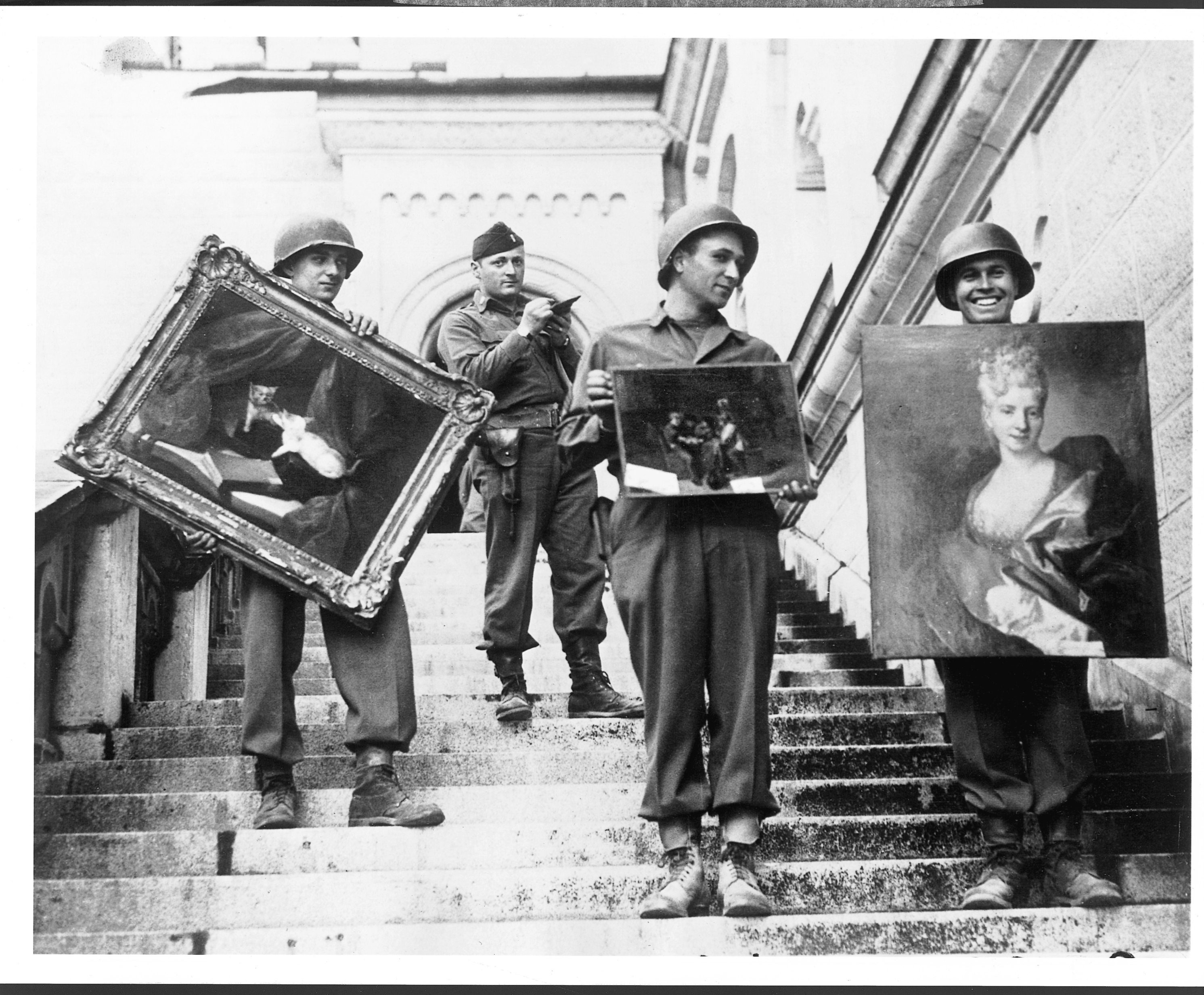 """art heists """"Monuments Man"""" James Rorimer, with notepad, supervises U.S. soldiers as they carry paintings down the steps of the castle in Neuschwanstein, Germany, in May 1945, Source: The Washington Post"""