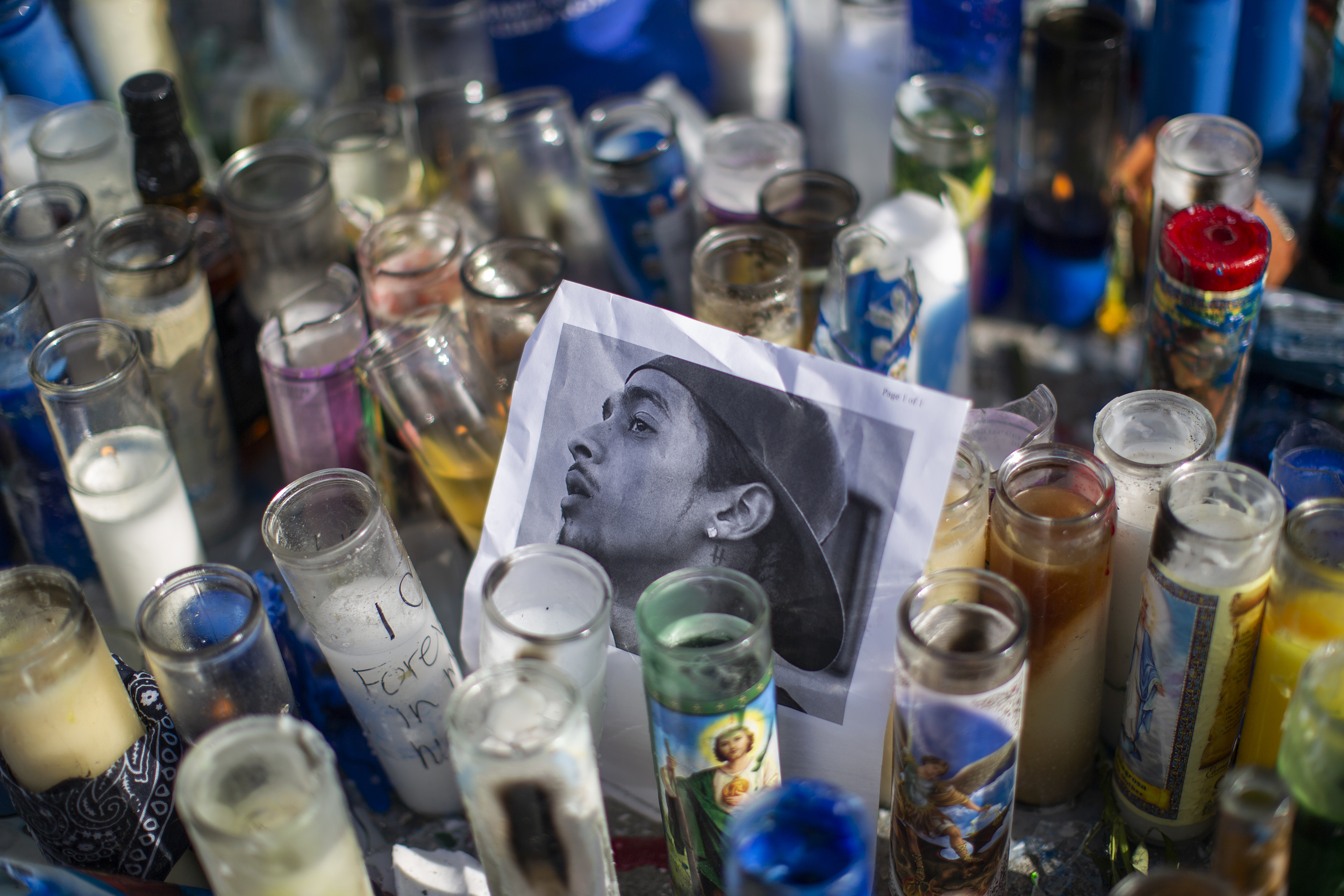 A photo of rapper Nipsey Hussle, 33, is seen among candles as people gather to mourn him on Monday in Los Angeles. (David Mcnew/Getty Images)