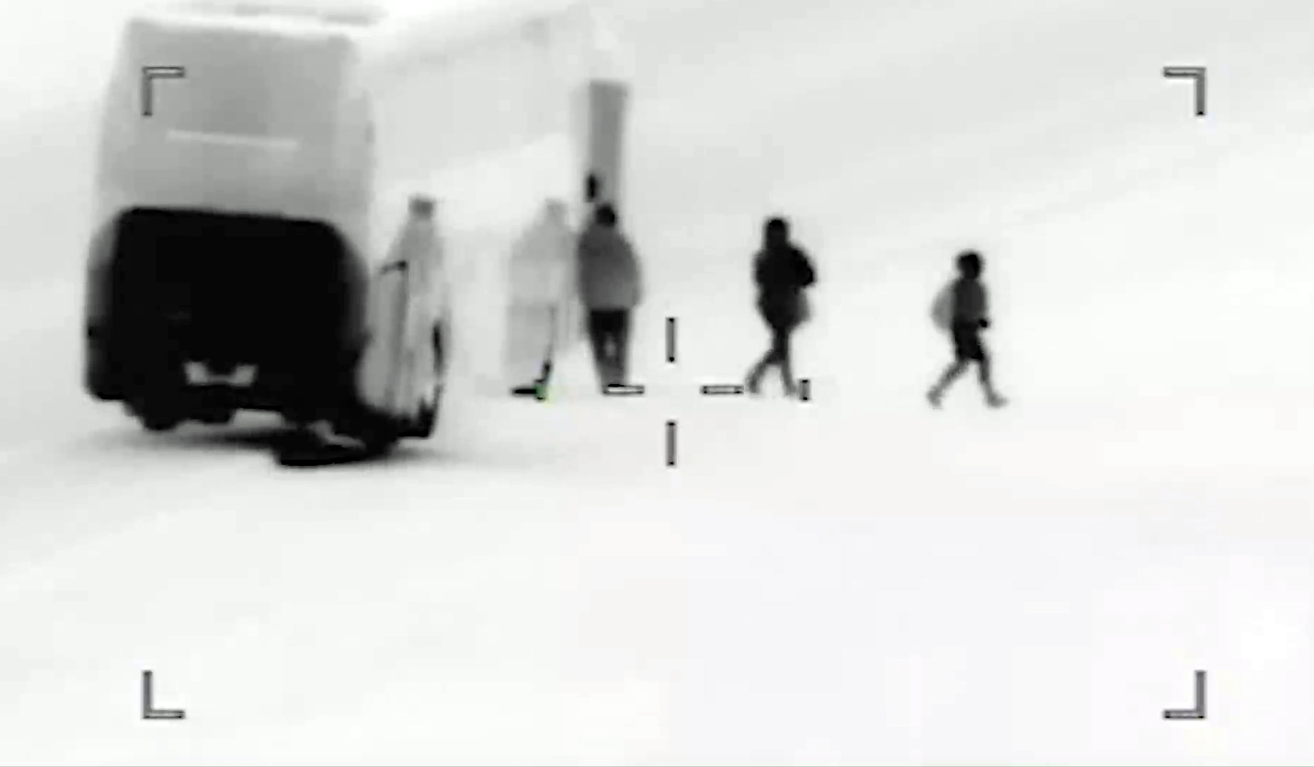 """This frame taken from U.S. surveillance video shows migrants disembarking from a bus in part of what U.S. officials call """"The Conveyor Belt."""" Migrants are dropped off within walking distance of the U.S. border."""