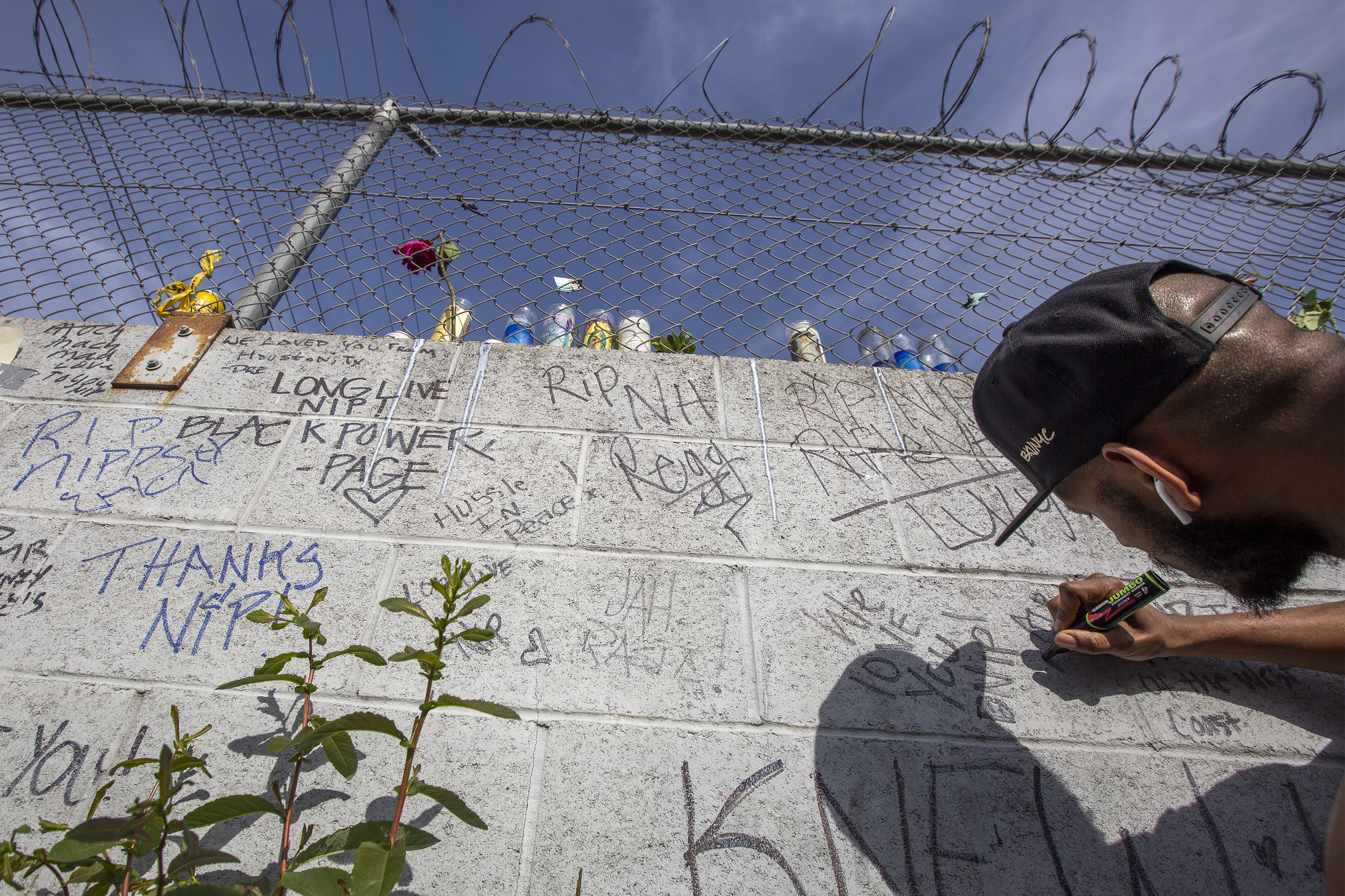 People write condolences to Nipsey Hussle on Monday in Los Angeles.