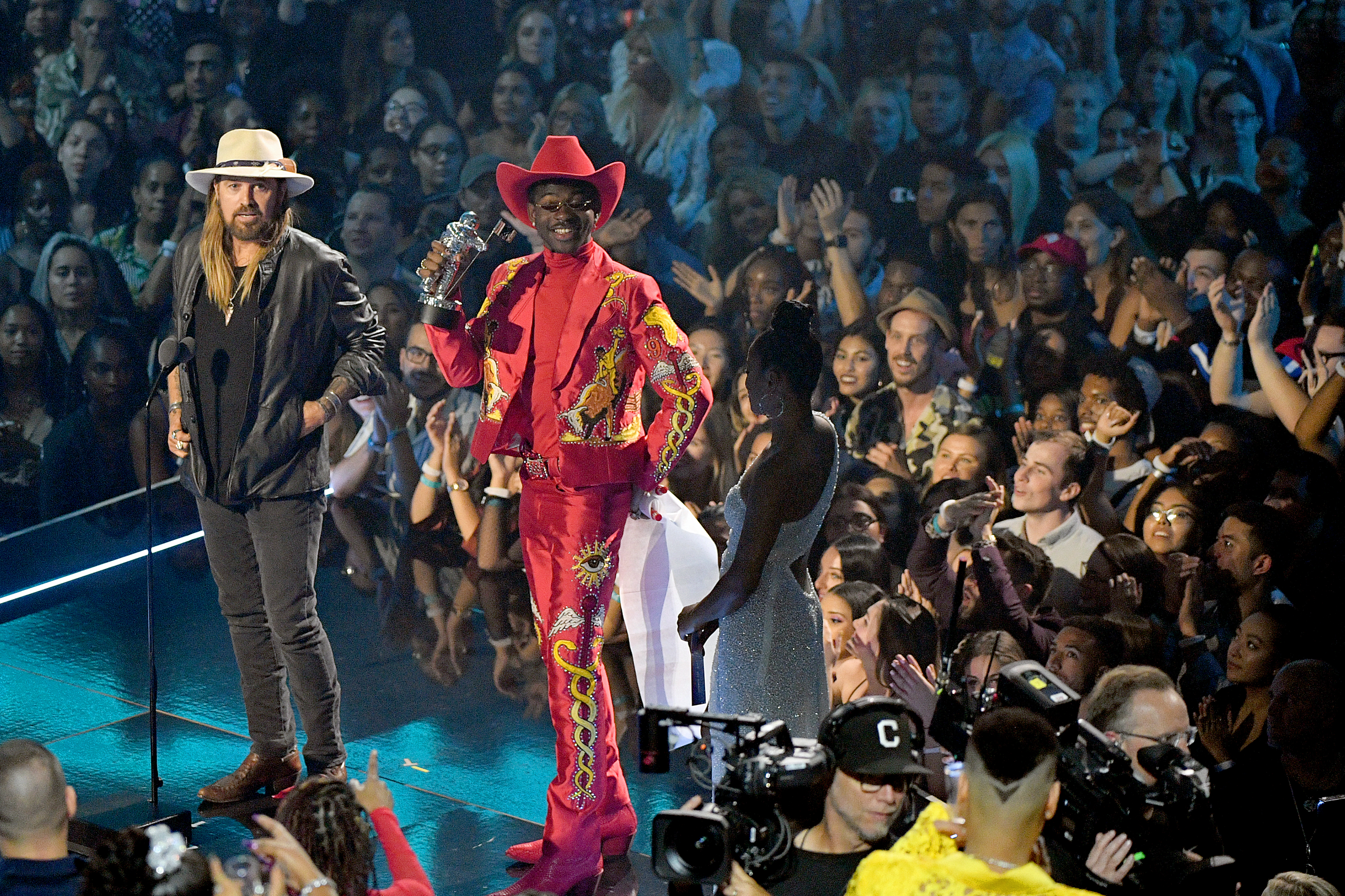 Billy Ray Cyrus and Lil Nas X speak onstage during the 2019 MTV Video Music Awards.