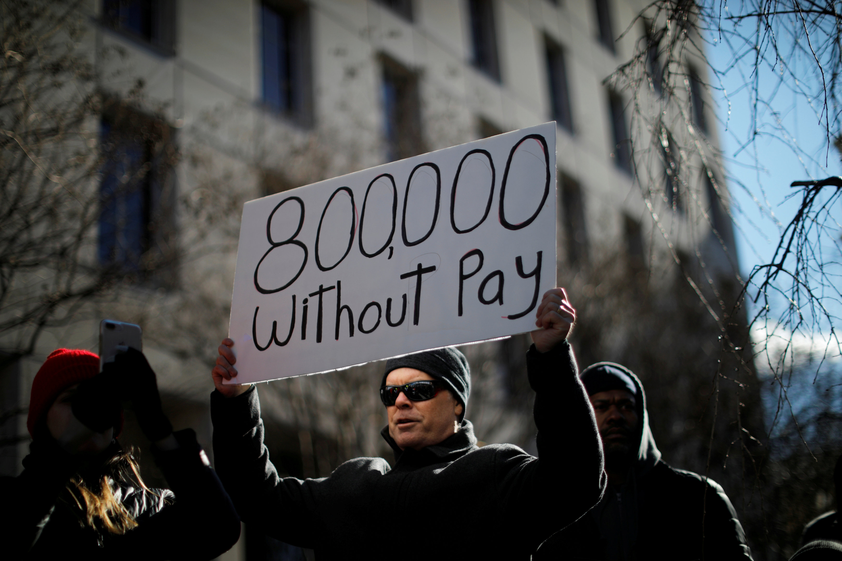 A demonstrator holds a sign, signifying hundreds of thousands of federal employees who won't be receiving their paychecks as a result of the partial government shutdown. REUTERS/Carlos Barria