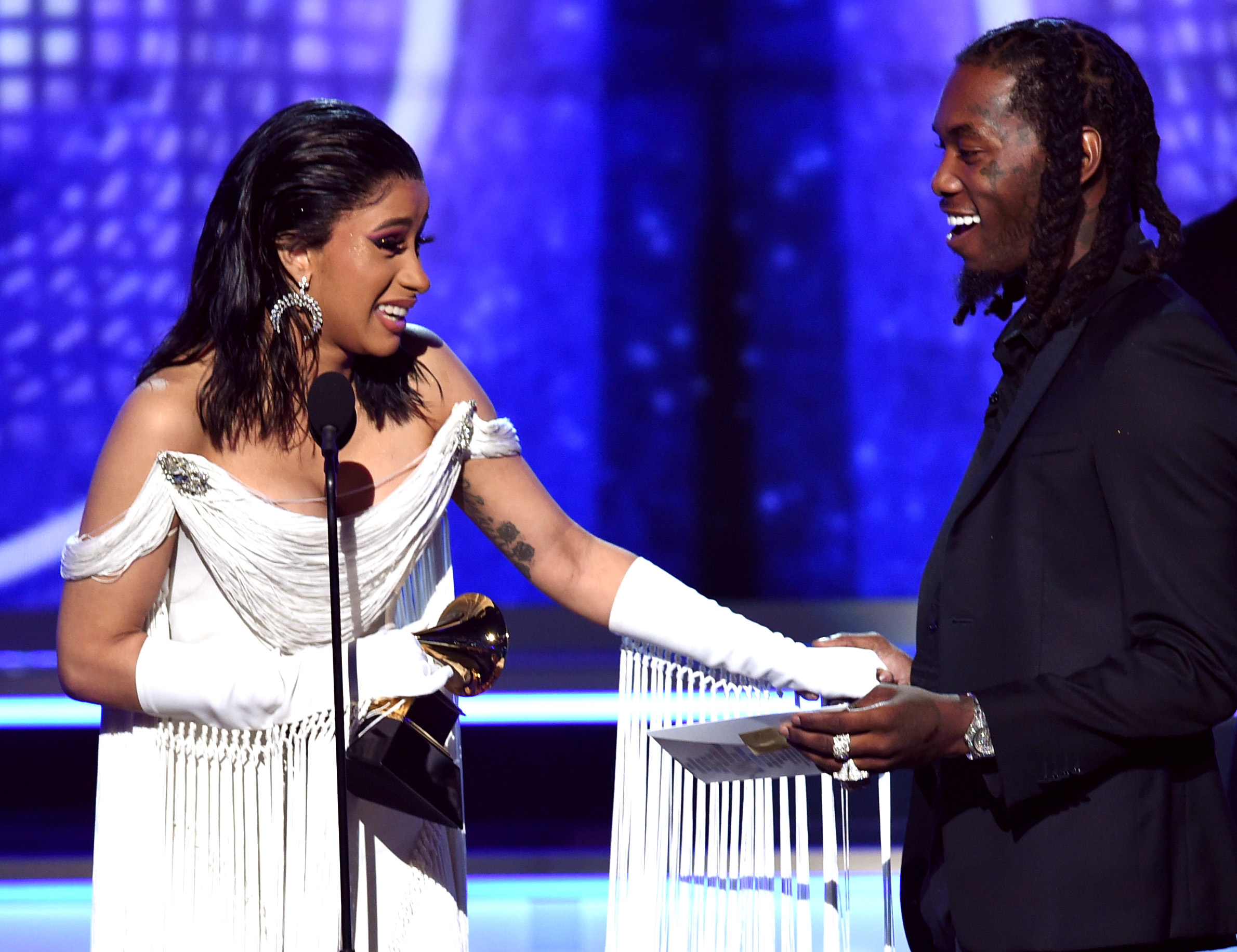 """Cardi B and Offset accept the best rap album award for """"Invasion of Privacy"""" onstage during the Grammys."""