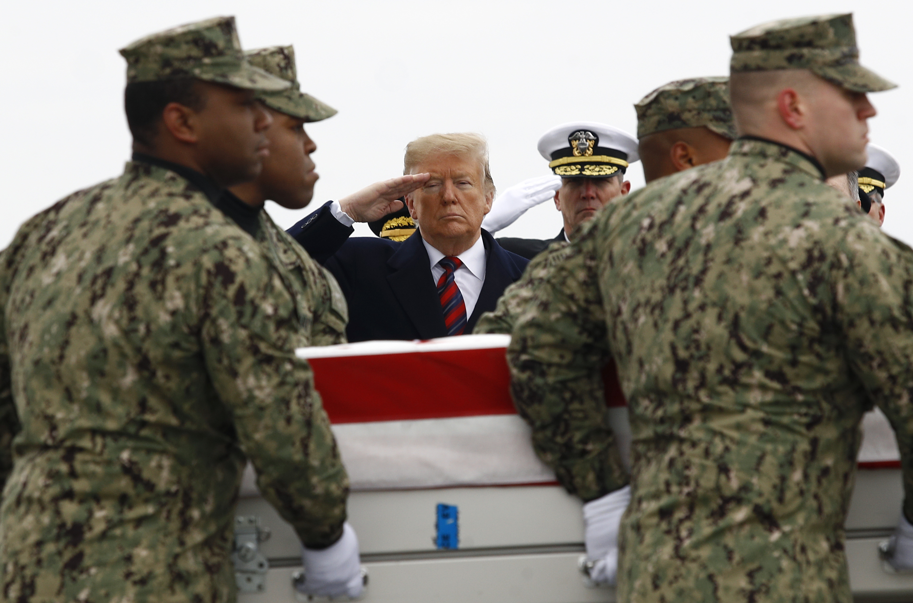 President Trump salutes on Jan. 19, 2019, as sailors move a coffin containing the remains of Scott A. Wirtz, a civilian and former Navy SEAL who was killed in a suicide bomb attack in Manbij, Syria. (Patrick Semansky/AP)
