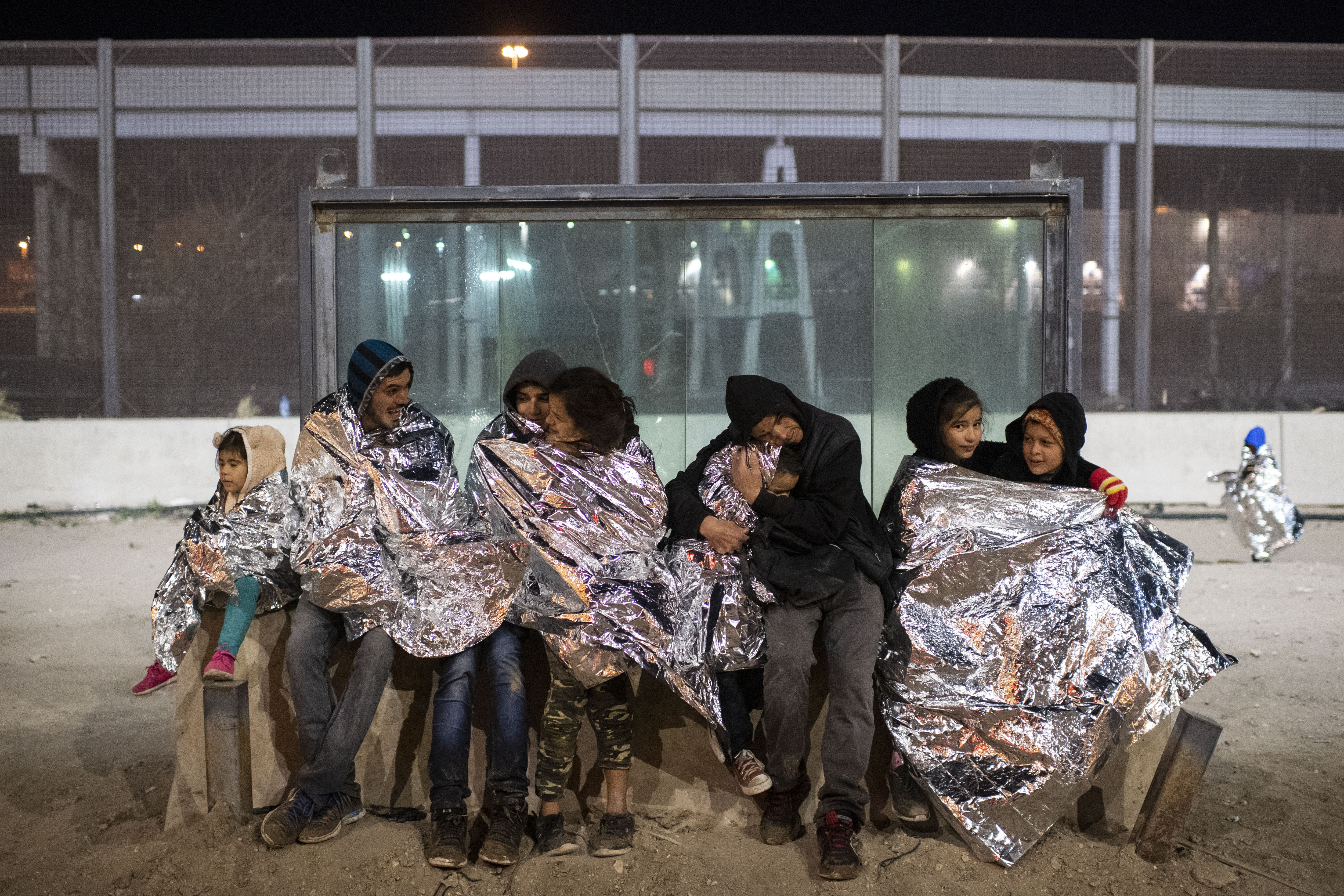 Central American migrants wrap themselves in Mylar blankets, which were distributed by Border Patrol agents, to brace against the near-freezing temperatures while they wait to be processed and transported to a holding facility in El Paso, on Feb. 22. The group of 64 migrants walked across the Rio Grande and presented themselves to Border Patrol agents.