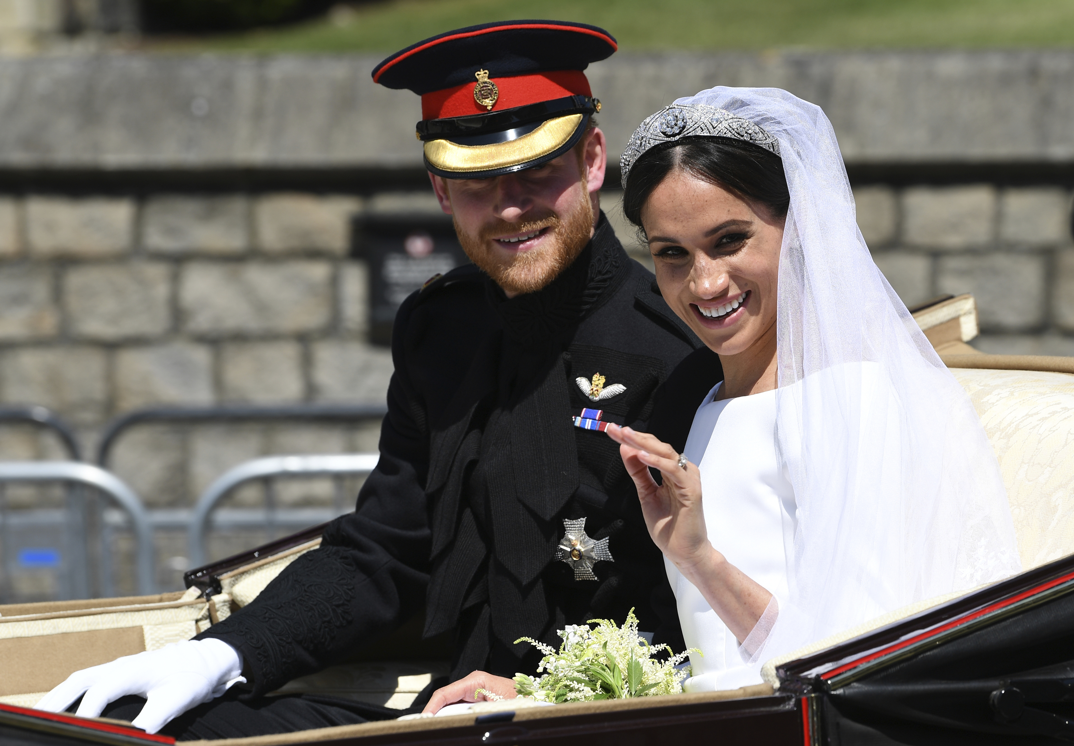 Prince Harry, Duke of Sussex and his wife Meghan Markle, Duchess of Sussex, wave from the Ascot Landau Carriage after their wedding ceremony. (Paul Ellis/pool photo via AP)