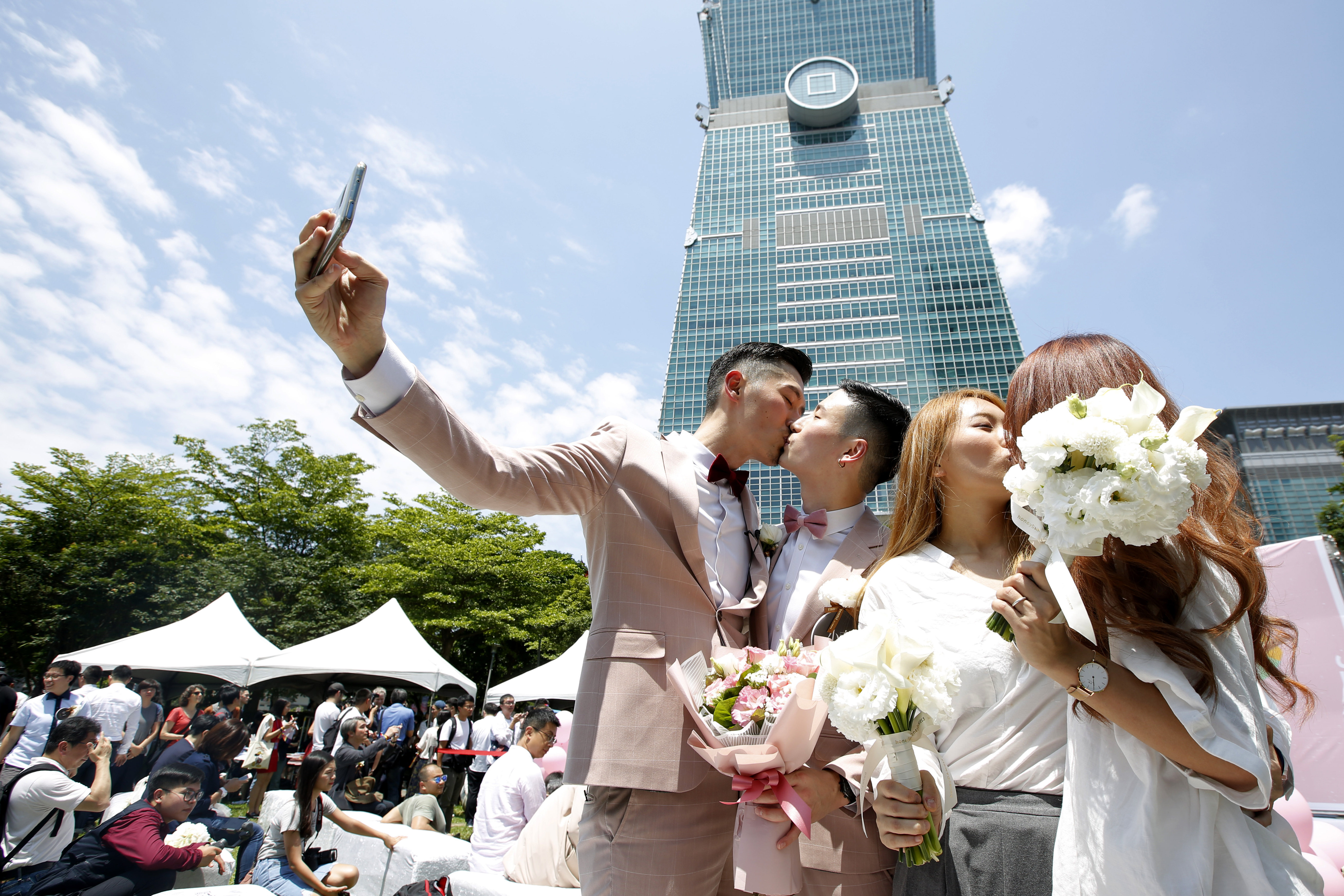 Married couples kiss while posing for photographs in front of the Taipei 101 building.
