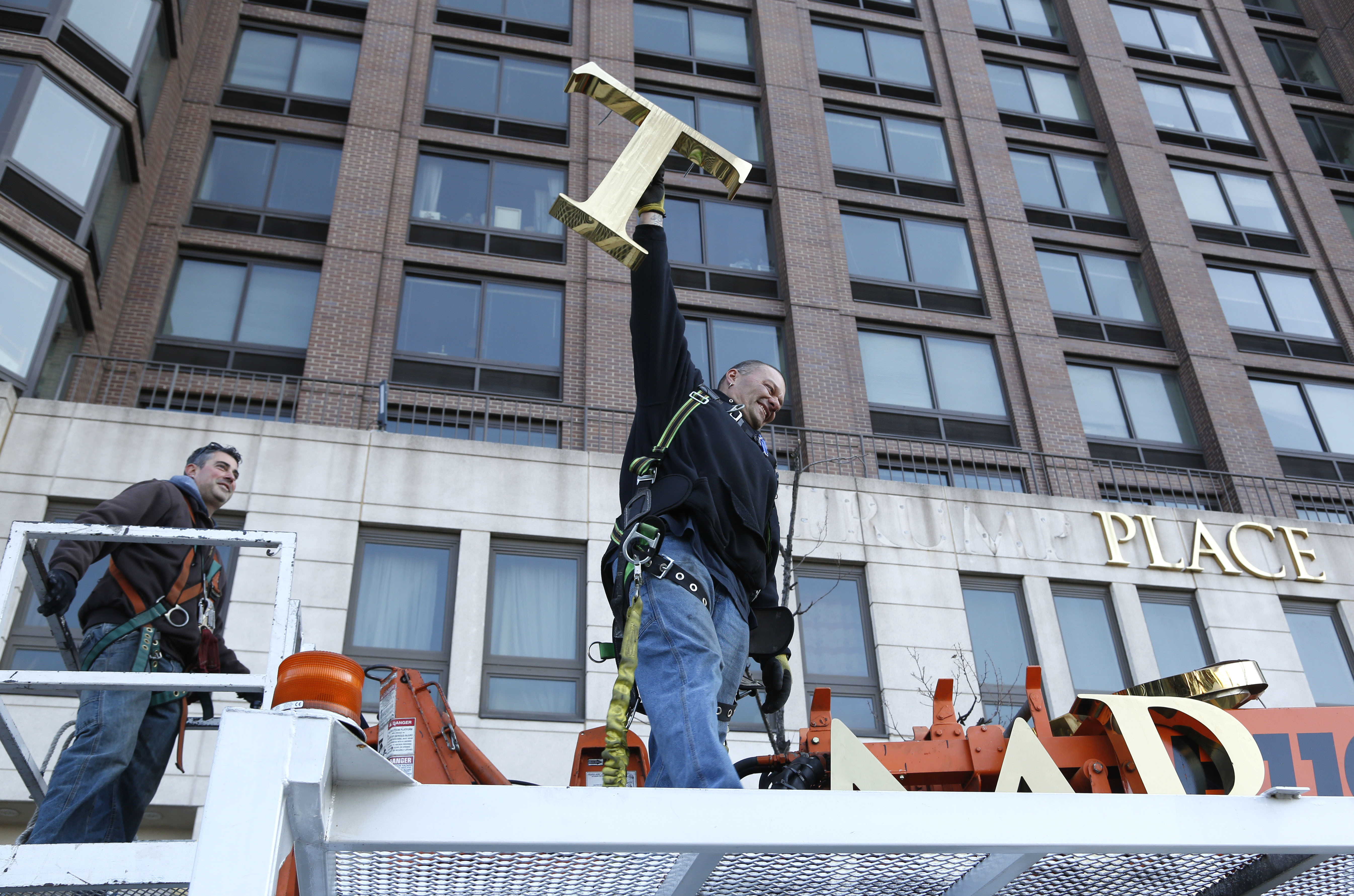 "A workman holds up the letter ""T"" in November 2016 as a crew removes the name from a New York building formerly known as Trump Place. Hundreds of tenants had signed a petition saying they were embarrassed to live in a place associated with the president-elect."