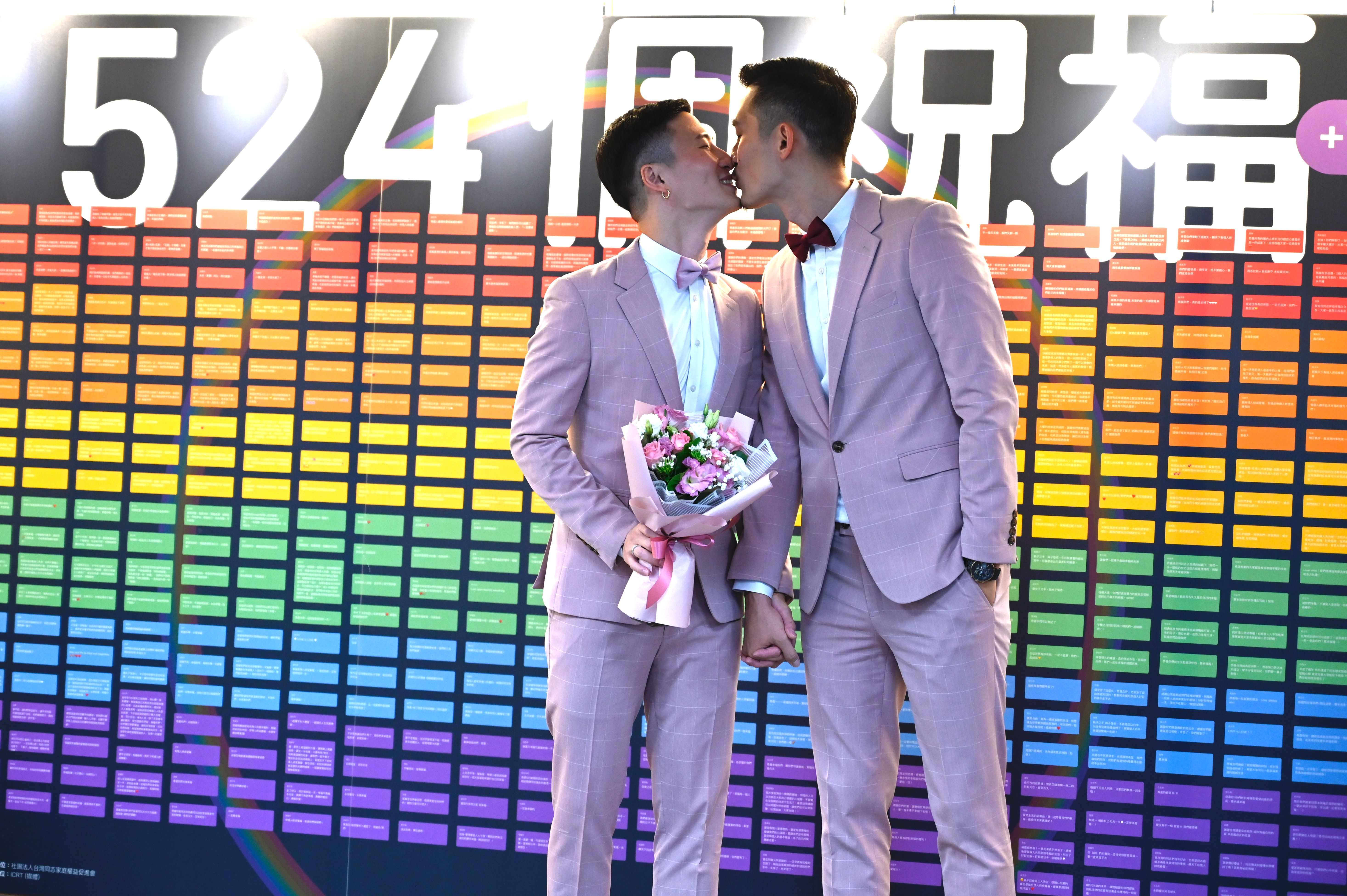 Shane Lin, left, and Marc Yuan kiss outside the Household Registration Office in Taipei on May 24.
