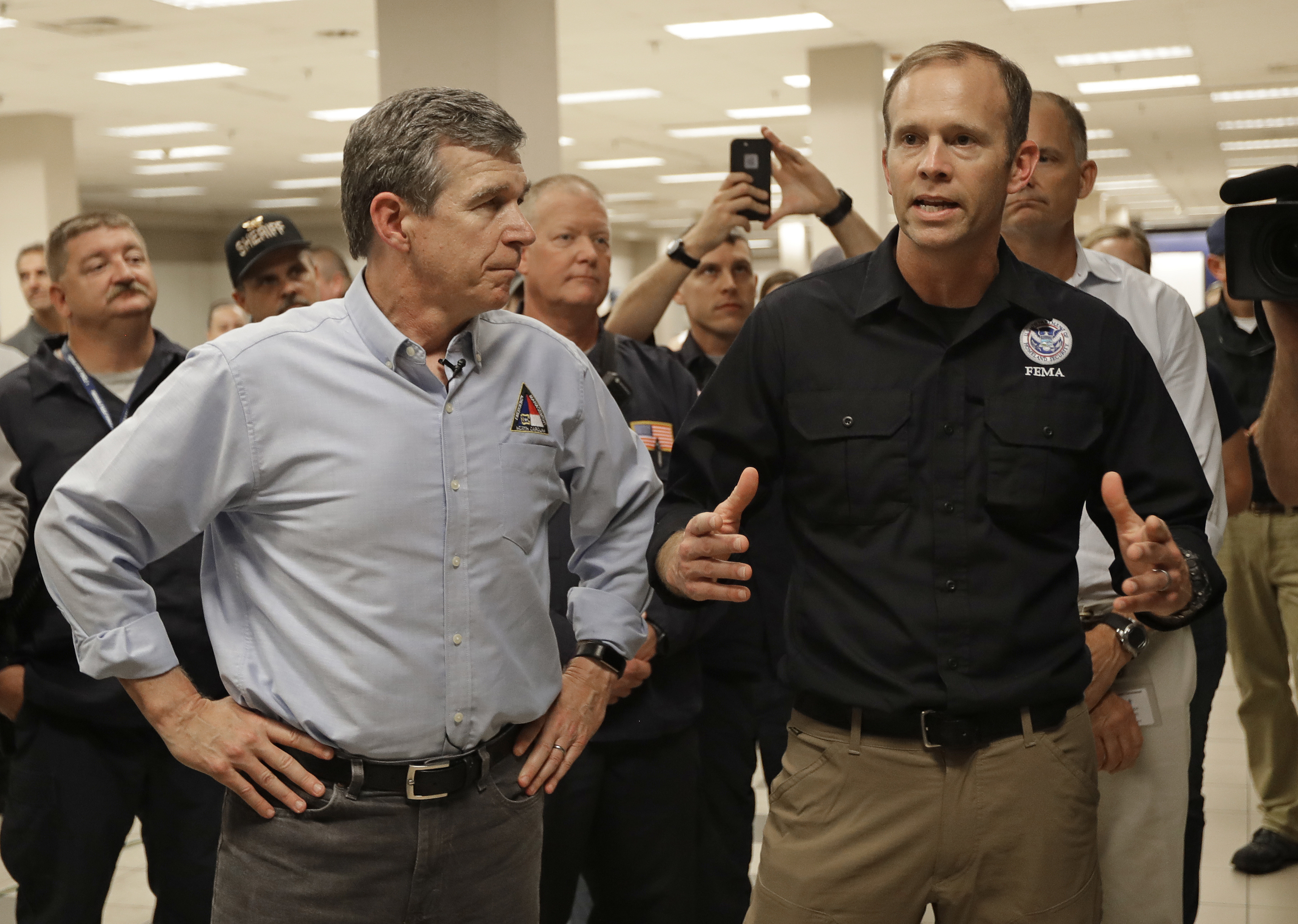 """Federal Emergency Management Agency Administrator William """"Brock"""" Long, right, and North Carolina Gov. Roy Cooper speak to emergency workers at a command center in Wilmington, N.C., on Sept. 18. (Chuck Burton/AP)"""