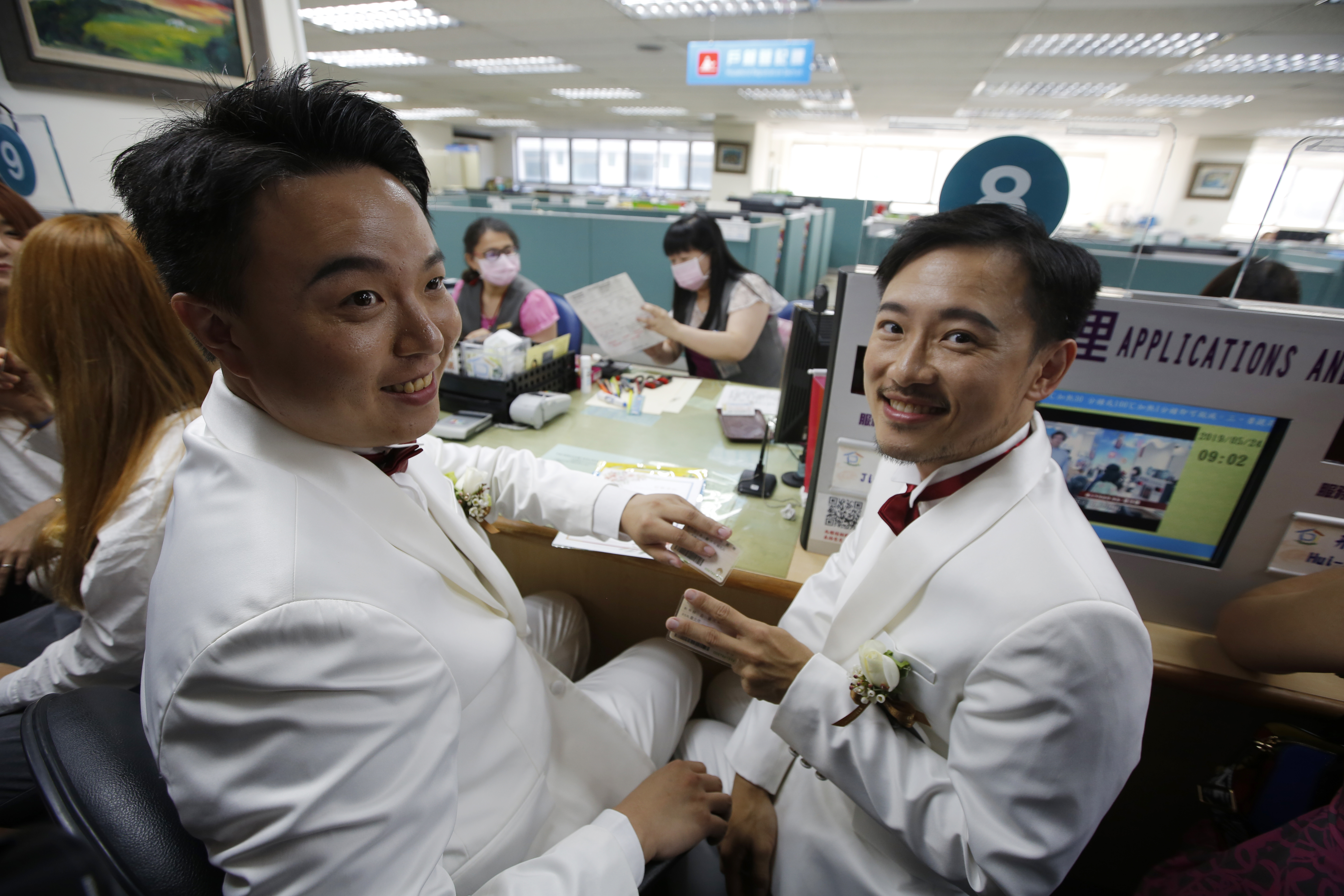 A couple holding identity cards poses for photographs while registering for marriage at a Household Registration Office. (Ashley Pon/Bloomberg News)