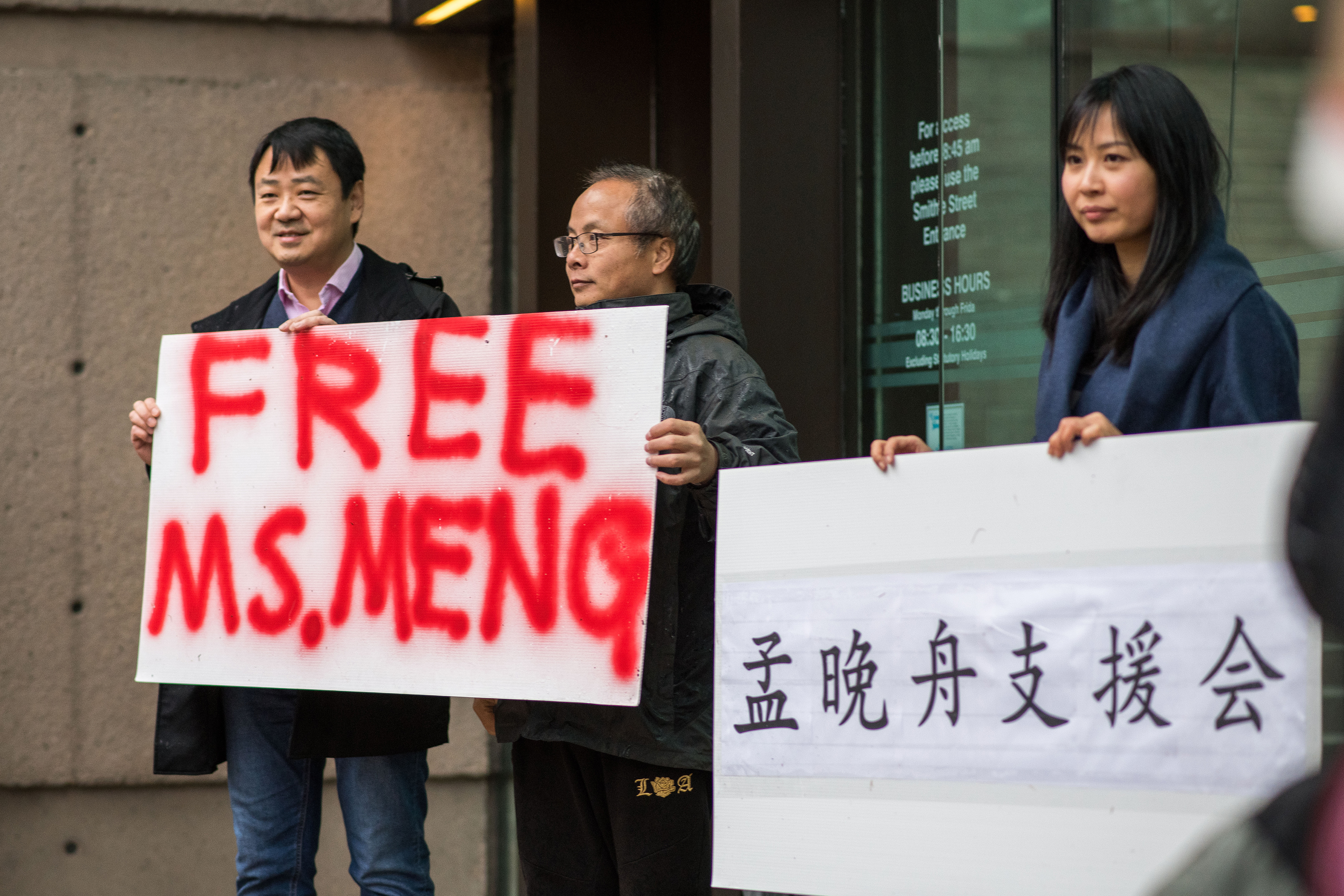 People hold signs in support of Meng Wanzhou, chief financial officer of Huawei Technologies. , outside a bail hearing at the Supreme Court in Vancouver on Dec. 11, 2018.