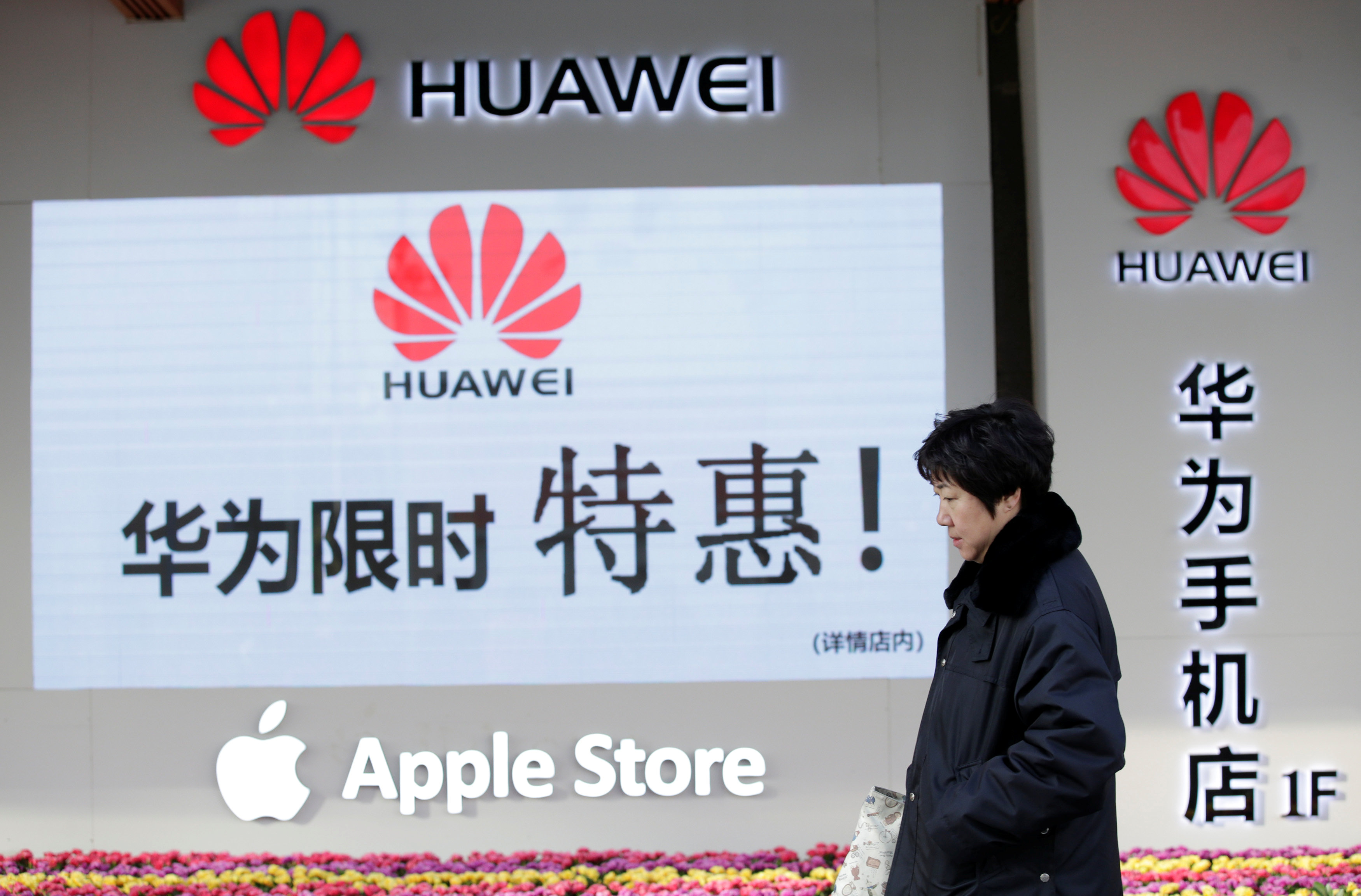 A woman walks past Huawei and Apple shops in Beijing on Dec. 12, 2018.