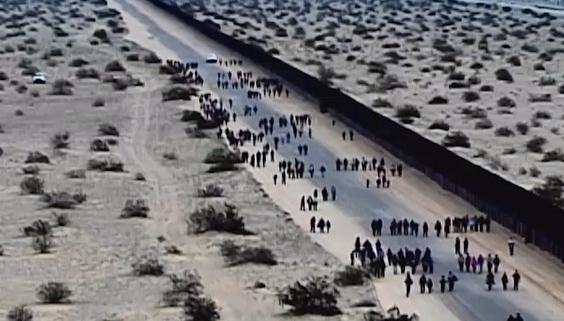 """This frame taken from video shows a large group of migrants arriving at the U.S. border, part of what U.S. officials call """"The Conveyor Belt."""" (U.S. Customs and Border Protection)"""